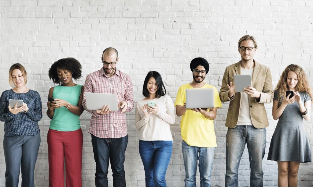 Pessoas observando seus tablets e computadores felizes impactados pelo web site que utilizou Contextual Marketing.